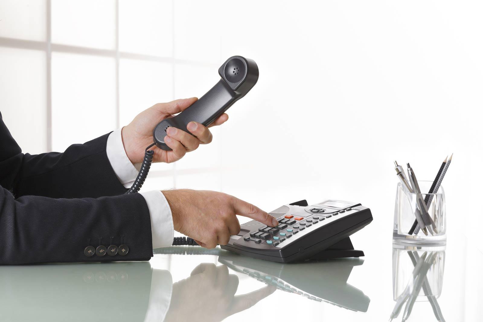 Businessman dialling a phone