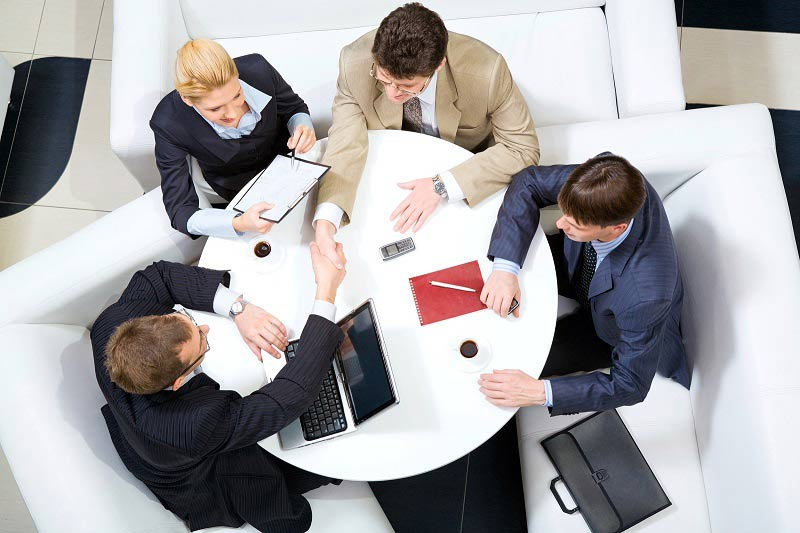Business people sat around meeting table