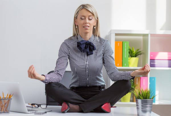Young woman meditating in office