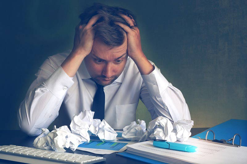 Businessman looking stressed with paperwork
