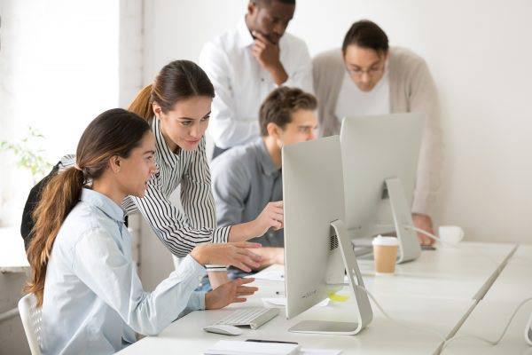 Team mentoring around laptops