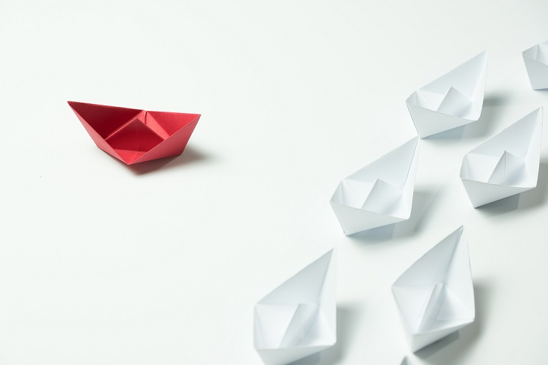 Red paper ship going in different direction