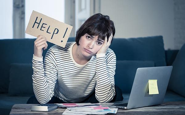 Portrait of worried and desperate woman feeling stressed paying credit card debts and bills on laptop computer on sofa at home. In business and home finances and financial problems concept.