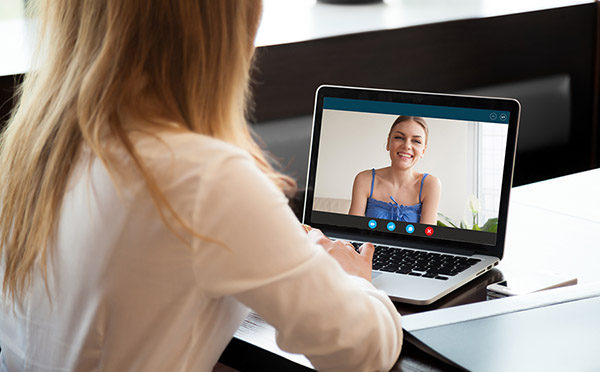 Two young women chatting online by making video call on laptop