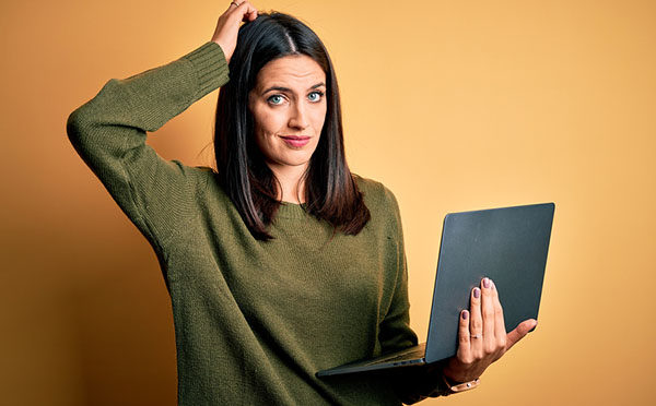 Young brunette woman with blue eyes working using computer lapto